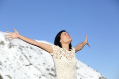 Happy woman breathing deep raising arms in winter Royalty Free Stock Photos