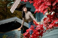 A Happy Woman Breathing Fresh Air in Autumn, Closed Eyes and Smiling in front of the House, Red Maple tree as foreground royalty free stock photography