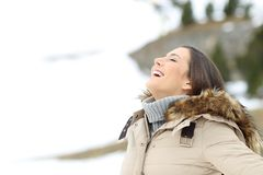 Happy woman breathing fresh air in winter holiday. In the snowy mountain stock image