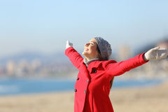 Happy woman breathing raising arms in winter. Happy woman wearing a red jacket breathing fresh air and raising arms on the beach in a sunny day of winter Royalty Free Stock Photo