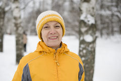The happy woman in a bright yellow cap and a jacke Stock Images