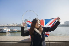 Happy woman with British flag against London Eye at London, England, UK Royalty Free Stock Photography