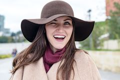 Happy woman in a brown hat and beige coat, winking one eye at the camera and smiles widely with white teeth. Pick me. stock photo