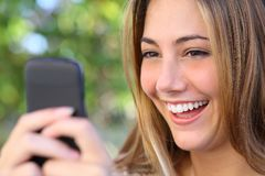 Happy woman browsing internet in her smart phone outdoor Stock Photo