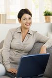 Happy woman browsing internet at home Stock Photography