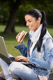 Happy woman browsing internet in park eating Stock Photo