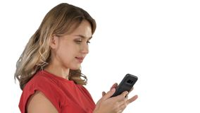 Happy woman browsing media or texting in a mobile smart phone on white background. stock image