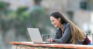 Happy woman browsing online content on a laptop. In a rural apartment terrace stock video footage