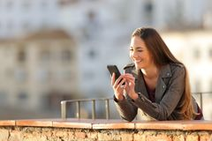 Happy woman browsing phone content at sunset in a balcony. Happy woman browsing smart phone online content at sunset in a balcony stock photography