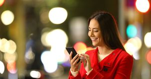 Woman browsing phone content in a winter night. Happy woman browsing smart phone content in a winter night in the street stock video footage