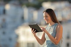 Happy woman browsing tablet content in a town stock image