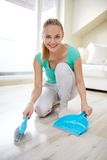 Happy woman with brush and dustpan sweeping floor Stock Photo