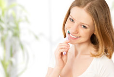 Happy woman brushing her teeth with a toothbrush Royalty Free Stock Image