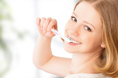 Happy woman brushing her teeth with a toothbrush. Healthy happy young woman with snow-white smile brushing her teeth with a toothbrush Royalty Free Stock Images