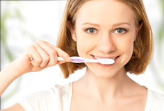 Happy woman brushing her teeth with a toothbrush Stock Photography