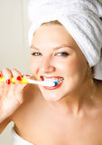 Happy woman brushing teeth Stock Images