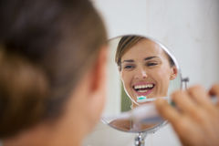 Happy woman brushing teeth with toothbrush Stock Image