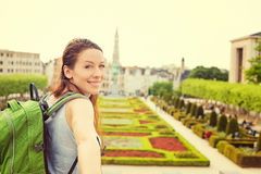 Happy woman in Brussels downtown extending you arm inviting to visit Mont des Arts garden. Happy young woman in Brussels downtown extending you an arm inviting Stock Image