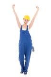 Happy woman builder in blue coveralls with hands up isolated on Royalty Free Stock Image
