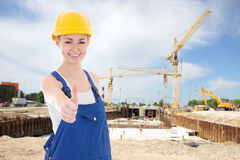 Happy woman builder in blue coveralls thumbs up Royalty Free Stock Photo