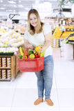 Happy woman buying fresh fruits and vegetables Stock Photo