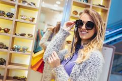 Woman buying sunglasses in shop stock photos