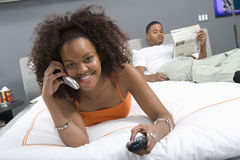 Happy Woman On Call While Watching TV In Bedroom Royalty Free Stock Photo