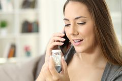 Happy woman calling doctor asking about bottle of pills Royalty Free Stock Photography
