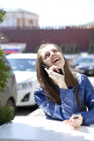 Happy woman calling by phone on the street Stock Photos