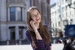 Happy woman calling by phone on the street Stock Photography