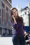 Happy woman calling by phone on the street Stock Images