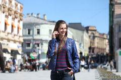 Happy woman calling by phone on the street Royalty Free Stock Images