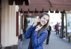 Happy woman calling by phone on the street Stock Image