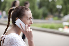 Happy woman calling by phone on the street. Young happy woman calling by phone on the street Stock Photos