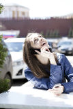 Happy woman calling by phone on the street. Young happy woman calling by phone on the street Stock Photo