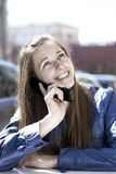 Happy woman calling by phone on the street. Young happy woman calling by phone on the street Royalty Free Stock Photo