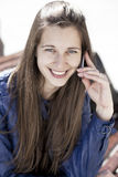 Happy woman calling by phone on the street. Young happy woman calling by phone on the street Royalty Free Stock Image