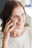 Happy woman calling on smart phone at restaurant Stock Images