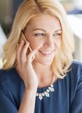 Happy woman calling on smart phone at restaurant Stock Photo