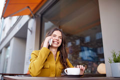 Happy woman calling on smartphone at city cafe Stock Images