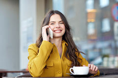 Happy woman calling on smartphone at city cafe. Communication, technology, leisure and people concept - happy young woman or teenage girl calling on smartphone royalty free stock images