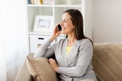 Happy woman calling on smartphone at home Stock Image