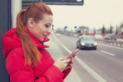 Happy woman calling a taxi with a smartphone app standing along the road. Woman calling a taxi with a smartphone app standing along the road stock photos