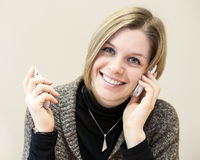 Happy woman calling with two mobile phones. At the same time Stock Photos