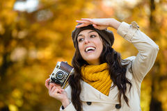 Happy woman with camera looking for autumn photo Royalty Free Stock Photo