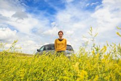 Happy woman with car among canola field Stock Image