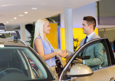 Happy woman with car dealer in auto show or salon Royalty Free Stock Images