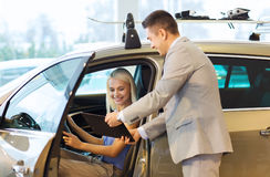 Happy woman with car dealer in auto show or salon Royalty Free Stock Photo