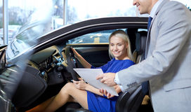 Happy woman with car dealer in auto show or salon. Auto business, car sale, consumerism and people concept - happy women with car dealer in auto show or salon Royalty Free Stock Photography
