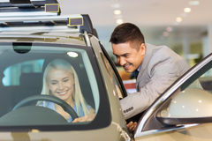 Happy woman with car dealer in auto show or salon Royalty Free Stock Image